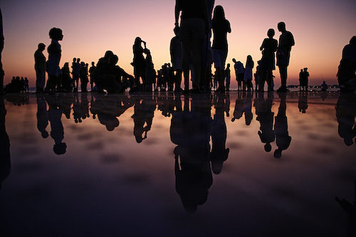 A bunch of people on a beach, as silhouettes