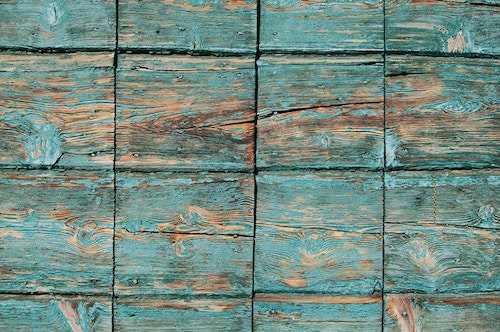 Flaky green paint on weathered planks